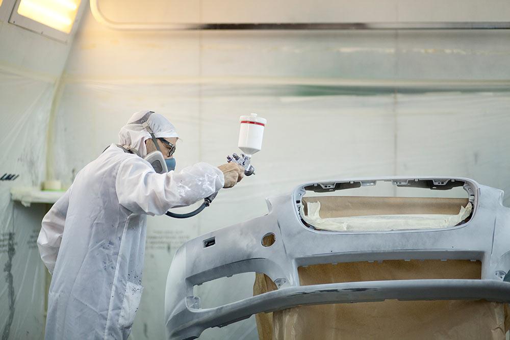 Hombre pintado un coche en el taller