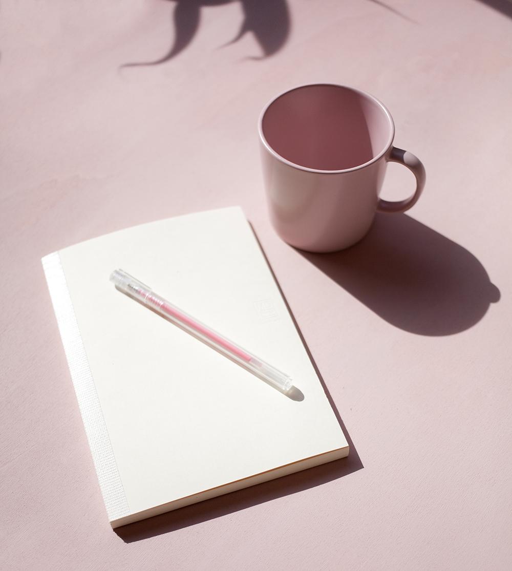 agenda blanca con boli y taza