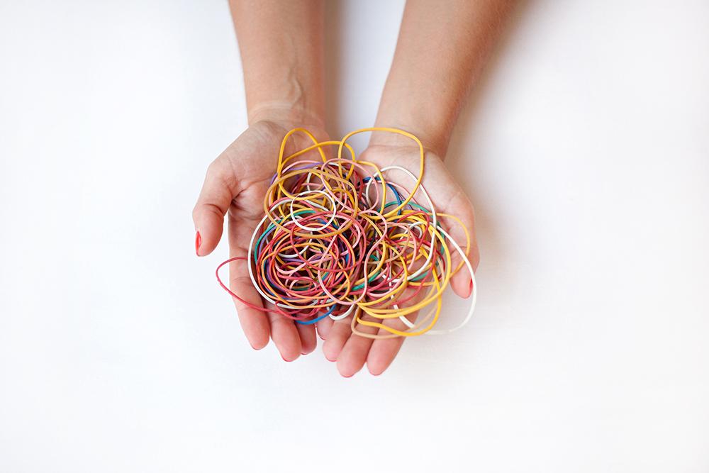 manos que sujetan gomas elásticas