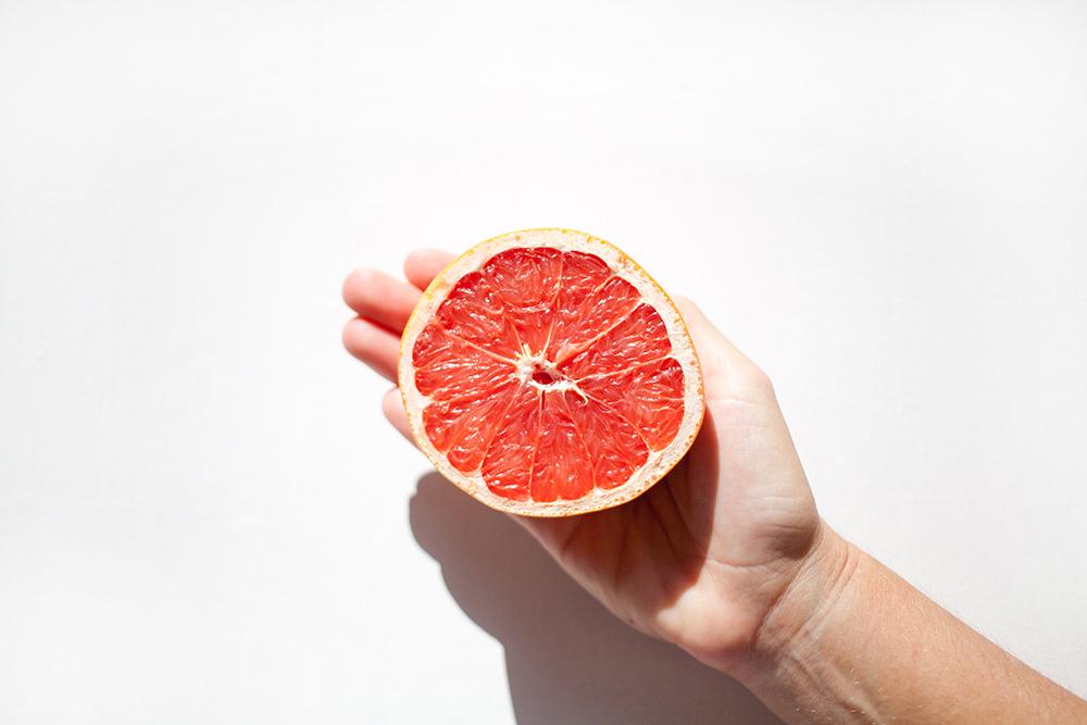 mano con medio pomelo