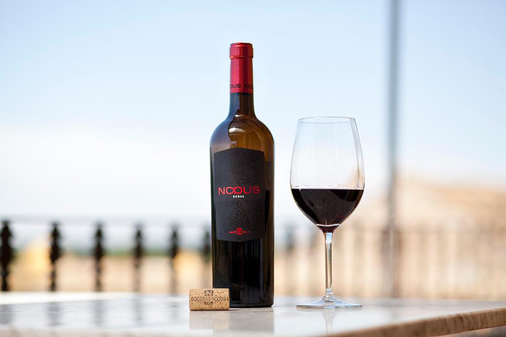 Botellas de vino tinto sobre bandeja en exteriores