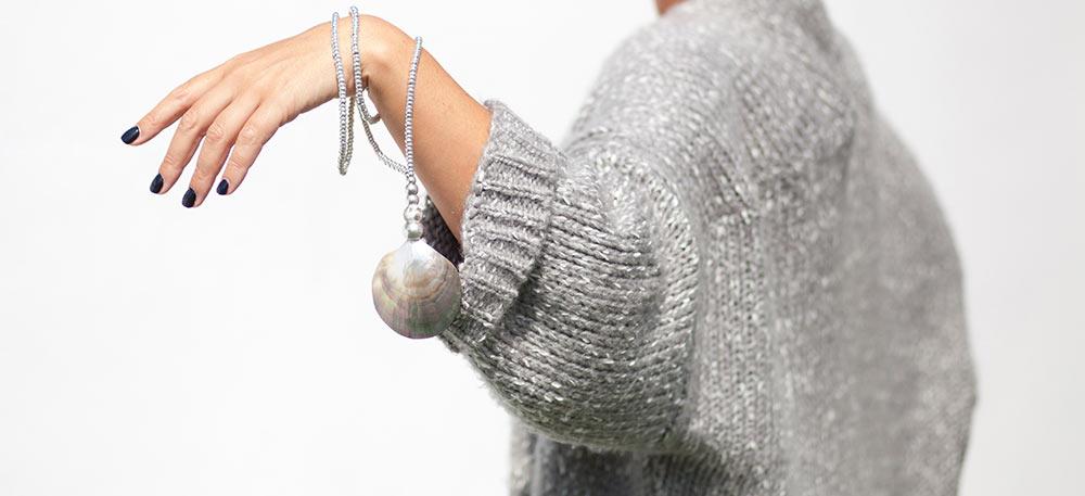 colgante en plata con concha en brazo de mujer